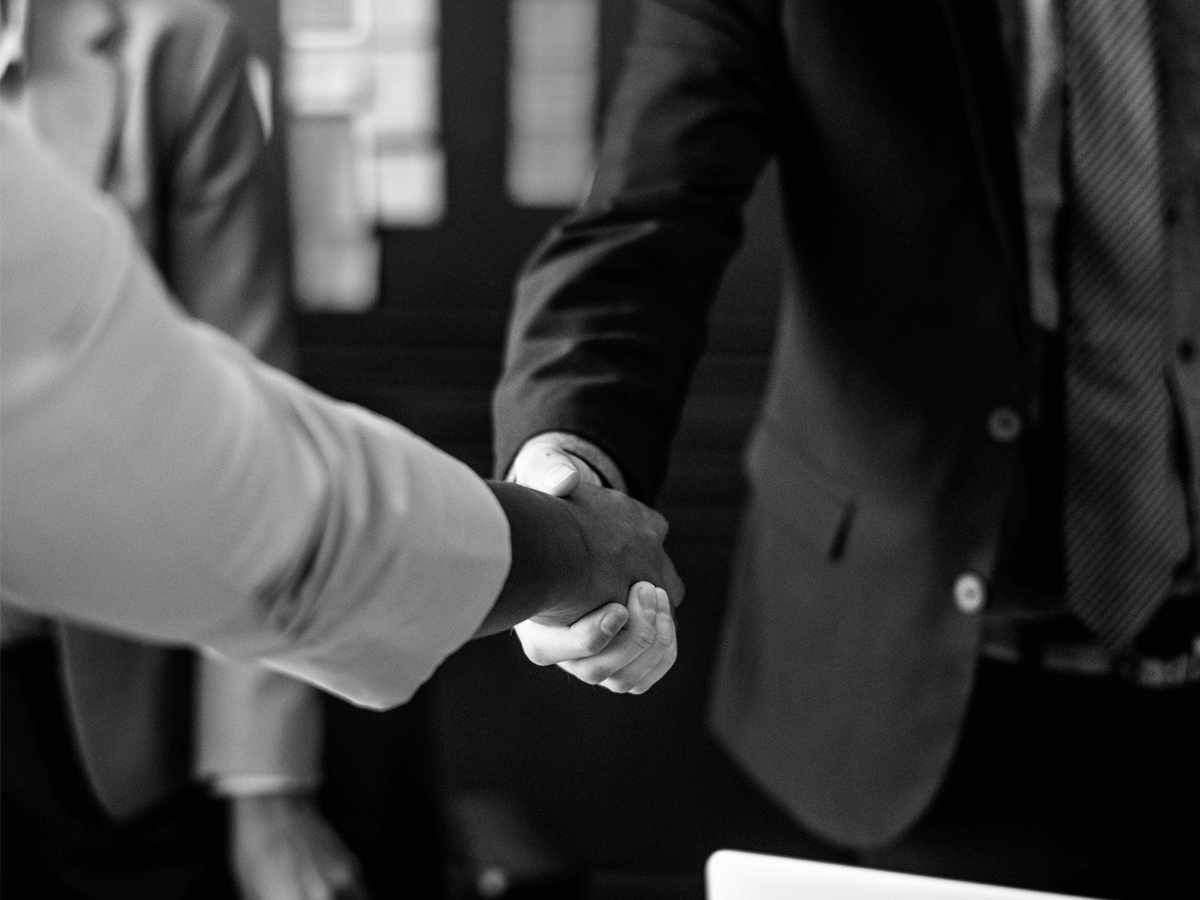 Two persons shaking hands representing the Customer Success strategy that Intercom is using while scaling.